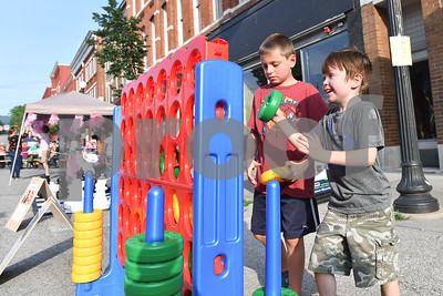 Jackson Bryson, 5, right, of Shrewsbury, and his brother Bryson, 9, center, go all out during a game of Connect 4 on Center Street in Rutland during the first Friday Night Live event of the summer. (Robert Layman / Staff Photo)