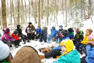 "Julia Bonafine, K-2 teacher at Shrewsbury Mountain School, reads ""In the Snow: Who's Been Here?"" to a group of kindgergarten and first graders around a fire at their outside classroom Thursday afternoon."
