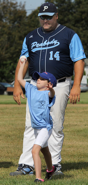 Peabody, Ma. 9-4-17. Olivia Silva who is suffering from cancerr, threw out the first pitch under the guidence of Officer Mark Bettencourt, Lynnfield PD, at the beginning of the 61st annual Peabody and Lynnfield charity baseball game at Emerson Park to raise money for cancer research.