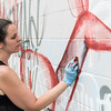 Elizabeth Kirby Sullivan works on her mural on the rear wall of Pick Up Modern.