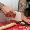 Michael Cucchiello Jr. cuts piecies of dough to make ricotta cookies at Cucchiello's Bakery in Saugus.