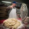 Michael Cucchiello Jr. sprinkles flour onto a pile of ricotta cookie dough at Cucchiello's Bakery in Saugus.