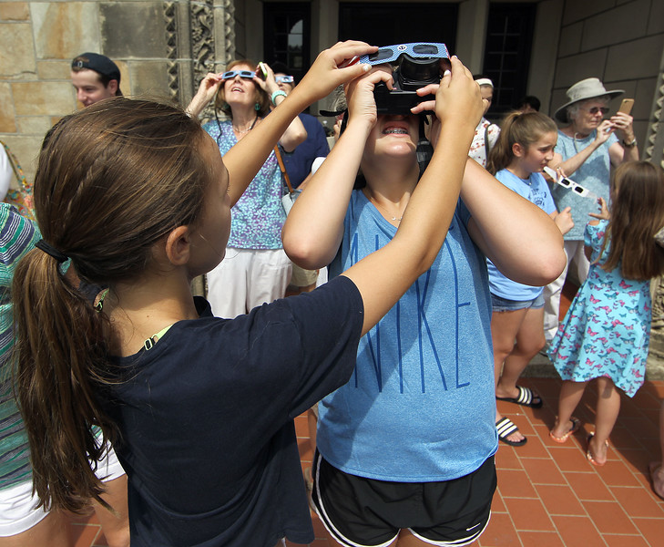 Nahant, MA Mon Aug 21, 2017- [l-r] Amelia Wyse holds eclipse viewing glasses in front of the camera lens of her friend Mariel Fulghum so she can photograph the eclipse  at the steps of the Nahant Library. <br /> <br /> Item Staff Photo/Jim Wilson
