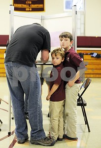 Robert Layman / Staff Photo  Jack Fortier, right stands with a hand on top of his younger brother Cash's head as their father Keith bubbles in a ballot during general election voting at Christ the King School Tuesday night.