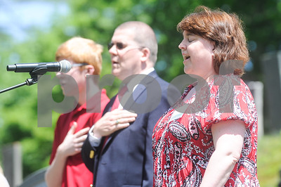 Robert Layman / Staff Photo Jennifer Sayles Harville sings the national anthem in front of President Calvin Coolidge, her great grandfather's, gravesite at Notch Cemetery in Plymouth July 4.