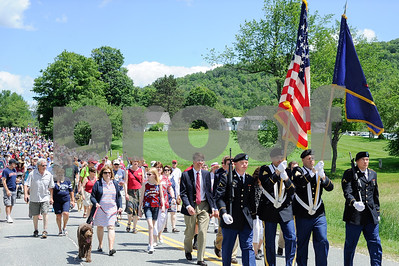 Robert Layman / Staff Photo Members of the Vermont National Guard proceed with the colors behind a parade of people as they march their way to Notch Cemetery for a wreath laying at the gravesite of President Calvin Coolidge on July 4, 2017.