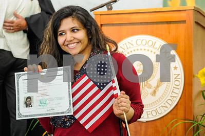Robert Layman / Staff Photo Garima Sahay, formerly of India,  poses with an American Flag and her certificate of citizenship after a naturalization ceremony at the President Calvin Coolidge State Historic Site in Plymouth, July 4, 2017.