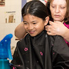 Mylee Tranle, 10, left, has her hair cut by Martha Mosquera for Locks for Love at Salemwood School in Malden on Saturday.
