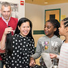 Salemwood Scool Assistant Principal Van Huynh holds up her hair that was cut by Jhon (correct spelling) Munera and shows it to students Manicha Exilhomme, 8, second from right, and Leianna Louis, 8, during the Locks for Love charity event at the school on Saturday.