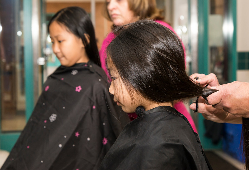 Sisters Abigail, 10, left, and Alexis Lee, 7, have their hair cut for Locks for Love during a charity event at Salemwood School in Malden on Saturday.