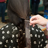 Sammi Nie, 13, has her hair measured before donating it to Lock for Love at a charity event at Salemwood School in Malden on Saturday.