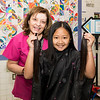 Abigail Lee, 10, of Malden holds up her hair that was cut by Martha Mosquera, left, during the Locks for Love fundraiser at Salemwood School in Malden on Saturday.