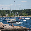Children hang out on rocks at Chandler Hovey Park as sailboats make their way out of Marblehead Harbor towards the start line of the Marblehead-Halifax Race in Marblehead on Sunday, July 9, 2017. (Scott Eisen/The Item)