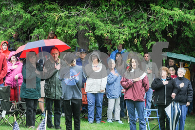 Robert Layman / Staff Photo Teh crowd joins together in the Pledge of Allegiance during Memorial Day Ceremony at the West Street Cemetery Monday morning.