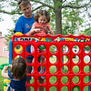 Nathan Bell lifts his daughter Lucy, 6, both of Nahant, up to play giant Connect 4 as Annie McNamee, 1, of Swampscott grabs a piece to play during the Builder's Club and Giant Game Day hosted by Nahant Public Library on Wednesday.