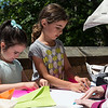 Avery Shaw, 6, left, and Eliana Uzcategui, 6, both of Nahant, learn how to make paper airplanes from Nahant Public Library Director Sharon Hawkes.