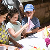 From left, Eliana Excategui, 6, Avery Shaw, 6, and Xavi Uzcategui, 4, all of Nahant, learn how to make paper boats during Paperpalooza.