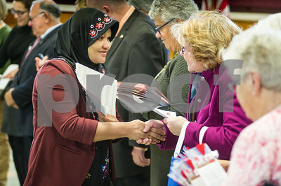 Robert Layman / Staff Photo Janet Be, formerly of Myanmar, recieves her citizenship papers during a naturalization ceremony at Christ The King School in Rutland Wedneday November 15, 2017.