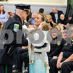 Robert Layman / Staff Photo Jared Harrington, new member of the Middlebury Police Department,  hugs his wife Nalani and daughter Gabriella before being pinned with his badge at the 103rd Bas ...