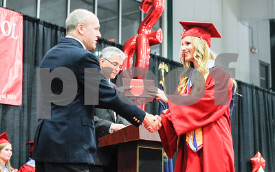 Robert Layman / Staff Photo Lauren Mary Cozzens, right, shakes hands with Dick Courcelle, Rutland Board of School Commissioners, while she recieves her diploma.