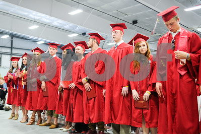 Robert Layman / Staff Photo Graduates stand with their diplomas.