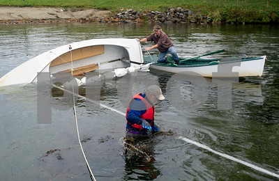 Robert Layman / Staff Photo  Joeseph Mark, center, pulls aquatic weeds from the mast of Quicksilver, his vacant sailboat that capsized during the storm late Sunday, early Monday, off the shore of Lake Bomoseen Thursday, Nov. 2, 2017. Joseph eventually was able to raise the mast and clear the boat from the lake. See the photo documentation of the groups recovery effort at www.rutlandherald.smugmug.com