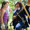 Salem Trayned Band member Mark Millman of Arlington shows Madelyn Sachs, 8, of Saugus how to load a musket at Saugus Iron Works on Wednesday.