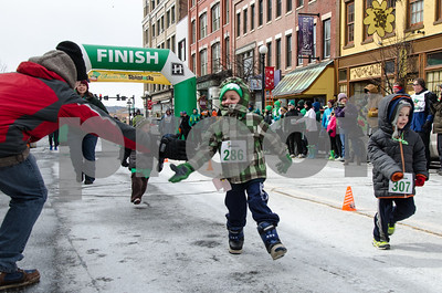 Robert Layman / Staff Photo A racer reaches ot to give a fan a high five during Shiver Me Shamrocks 5k in a frigid downtown Rutland Saturday afternoon.