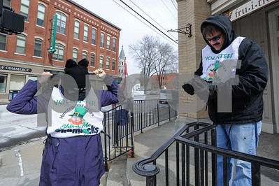 Robert Layman / Staff Photo Volunteers for the Shiver Me Shamrocks 5k suit up with their warmest winter gear Saturday on the corner of Merchants Row. Marleen Cenate, left and Marc Bates braved the cold and helped runners stay on course.