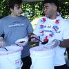 Swampscott, Ma. 7-2-17. Swampscott High football players Dimitri Hatzelamprou, left, and Nick Flint, right, prepare bowls of strawberry short cake from the 200 pounds of fresh strawberries at the Strawberry Festival at Swampscott Town Hall on Sunday.