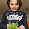 Anna Raslavicus, 8, grabs a freshly picked mint leaf from the garden at Summer Street School to add to her salad.