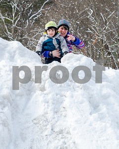 """Licoln Patterson, 3, of Rutland, and his mother Tiffany, play on a snowbank at Giorgetti Arena during Winter Fest's """"Go Play Day at Giorgetti"""" Sunday morning. (Robert Layman / Staff Photo)"""