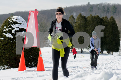 With winter scenery but not winter temperatures, runners found it difficult to predict a wardrobe for the Forsty Feet 5K. Seen here Erica Wallstrom runs through the first lap. (Robert Layman / Staff Photo)