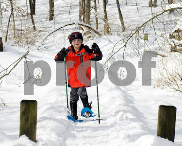 """Brayden Cannucci, 7, warms up on his snowshoes before trekking into the wilderness of Pine Hill park with his sister during Winter Fest's """"Go Play Day at Giorgetti"""" Sunday morning. The Rutland City Recreation Department sponsored event had free snowshoeing rentals for kids and adults. (Robert Layman / Staff Photo)"""