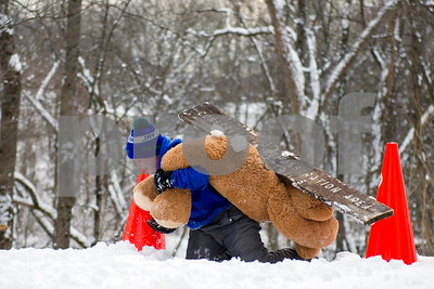 Finn Fuller, 8, takes out a board obstacle, incruing a second penalty as he competes in the Teddy Bear Carry Sunday morning at Giorgetti Park during Rutland's Winterfest Feb 18, 2018. Fuller and his brothers Wyatt and Will were fierce competitors that ran the course several times trying to beat their siblings record. (Robert Layman / Staff Photo)