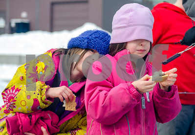 Olivia Guevin, left and her twin sister Isabelle, of Rutland enjoy their smores during Winterfest's Go Play Day at Giorgetti Sunday morning. (Robert Layman / Staff Photo)
