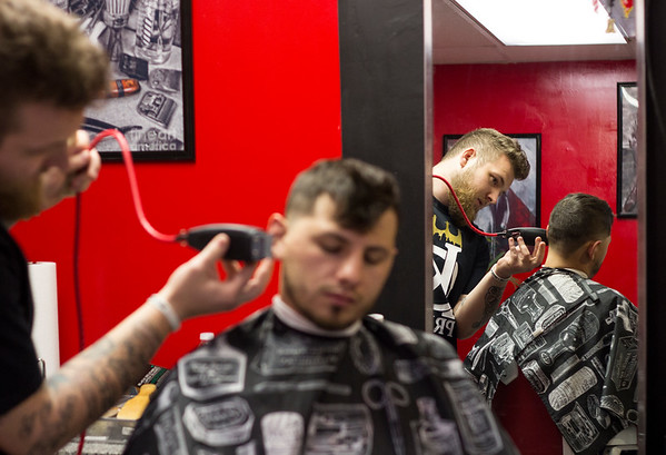 Spencer Wright cuts Mike Garcia's hair at Ink Therapy on Friday. As a Marine, Wright used to cut hair in combat zones. He loved it so much he decided to use his GI Bill to attend cosmetology school to become a barber.