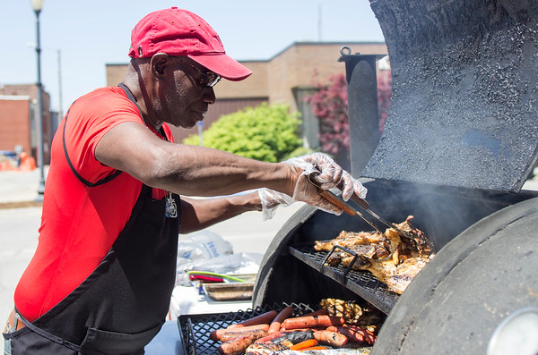 "Greg Armstrong prepares for the lunch rush in front of Rent-A-Center on South Market Street. Armstrong runs a food cart called ""A Taste of Heaven BBQ"" in Fairfield and has decided to expand his business to Ottumwa because he says there are a lack of meat-eaters in Fairfield. He says that he has been barbecuing for 20 years and was a head chef for 27 years before that. ""A Taste of Heaven BBQ"" will be open Wednesday through Saturday from 11 a.m. to 2 p.m. and 3 to 5 p.m."