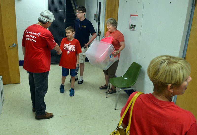 Walt Unterberger,  left,  associate pastor of Jarrettown United Methodist Church greets volunteers arriving to help ready the Mattie N.Dixon North Hills Community Cupboard.    Second from left is Patrick Daly with his brother William and grandmother Laure Evard.    Tuesday,  July 30, 2014.   Photo by Geoff Patton