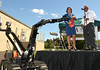 A Knight Robot hands a package to Montgomery County District Attorney Risa Ferman during a ceremony at WM Robots LLC in Colmar, a manufacturer and vendor of specialized equpment, including robots,  for military and law enforcement applications.   The Knight Robot is an all-terrain, remotely controlled robot that is equipped with cameras and the ability to disarm explosive devices.   It will be used by the North Penn Tactical Response Team and other police units working in Montgomery County .  Company employees donated the unit to the District Attorney's office as a measure of goodwill and as a symbol of their committment to the first-responder community.   At right is WM Robots Chief Operating Officer Gene Samsi.     Thursday,  August 28, 2014.   Photo by Geoff Patton