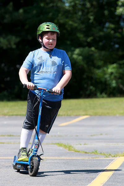 With his helmet on for safety Chase Abuuchon, 8, tired out his motorized scotter in the parking lot of the Leominster Eagles Club Post 477 on Tuesday afternoon with his friends as his mom watched.  SENTINEL & ENTERPRISE/JOHN LOVE
