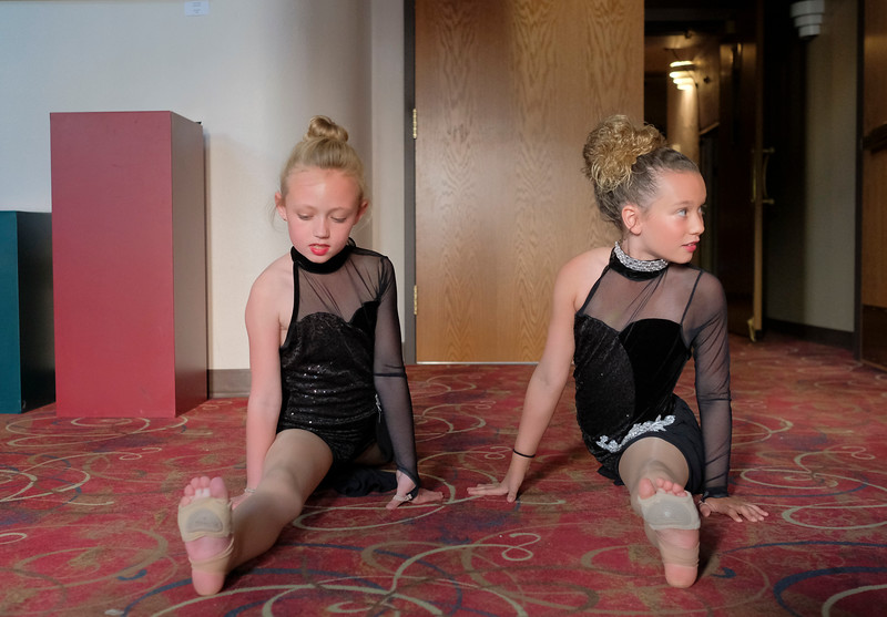 "Justin Sheely | The Sheridan Press<br /> Eight-year-old Natalie Busch, left, and Amya Neeriemer, 9, do a quick stretch in the lobby during a rehearsal for Donna's Dance Academy ""United Through Dance"" show Thursday at the WYO Theater. The event shows Friday and Saturday at 6p.m. and 8p.m."