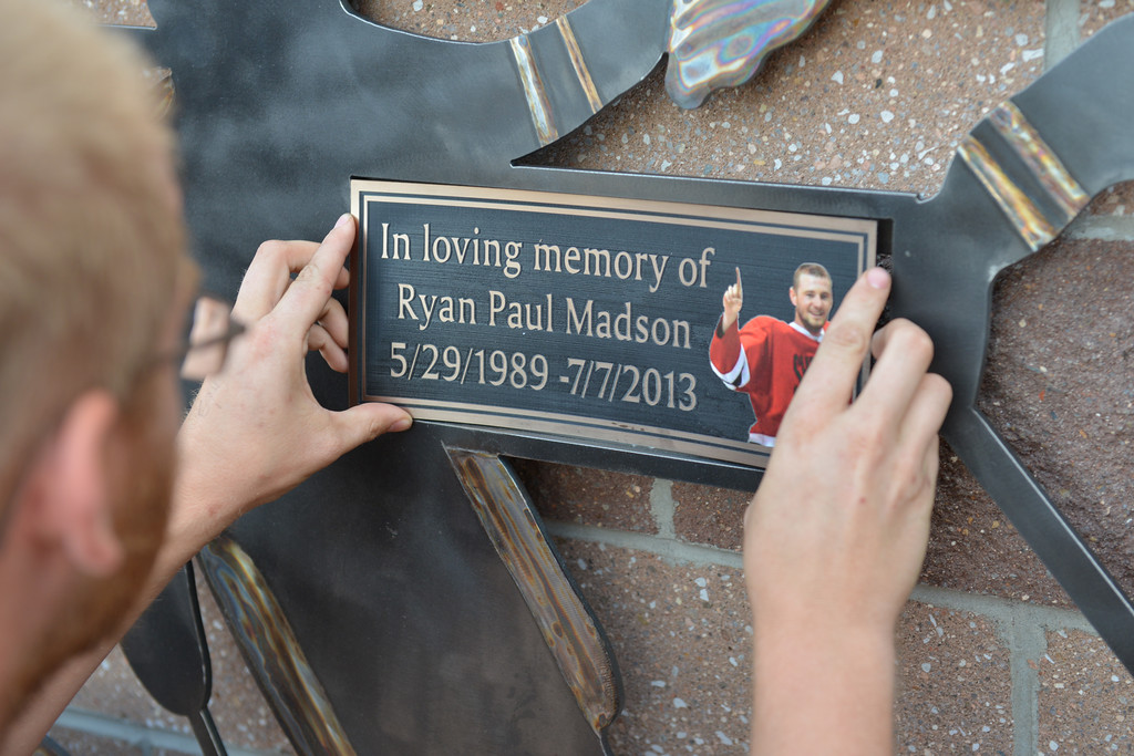 Justin Sheely | The Sheridan Press<br /> Chris Brown installs a plaque on the bench dedicated to the memory of Ryan Madson, 1989 - 2013, on Thursday at Whitney Rink in the M&M's Center. The Madson family raised funds to build the bench in honor of Ryan Madson, who loved and played adult league hockey at Whitney Rink. Craftco built the bench and donated much of the materials. ABC Signs also donated the permanent bronze plaque, which will be installed in a few weeks. Friends and family came to remember Ryan during the dedication of the bench.