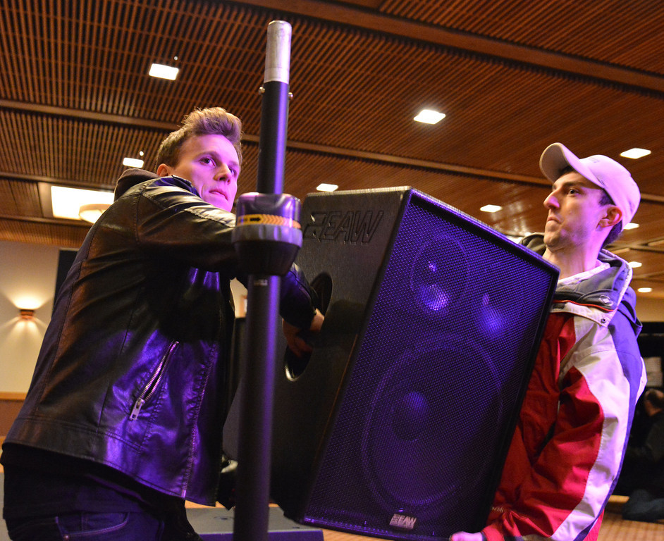Lancifer, left, and Steve Moyer lift a speaker onto the stand during setup for Lancifer in concert Friday at the Best Western Sheridan Center.