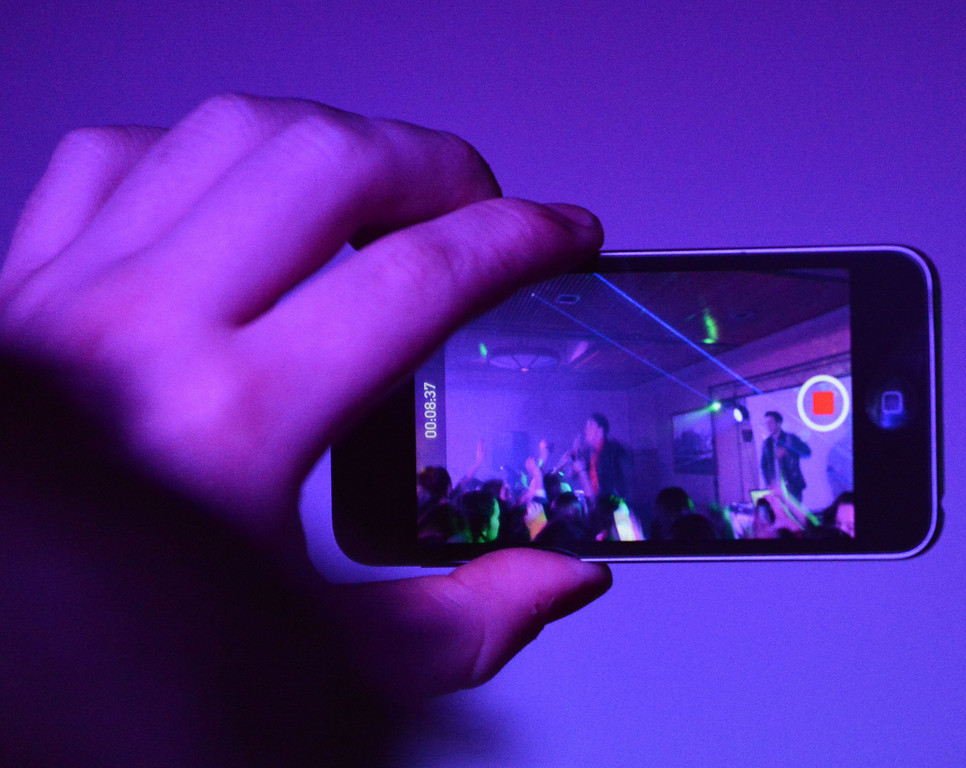 A fan records video on an iPhone during the concert