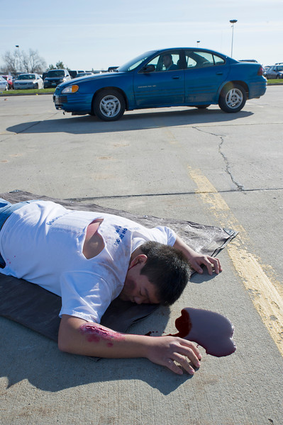 """Sheridan High School student Jin Kim lies motionless on the school parking lot Friday before the start of """"Last Call,"""" a mock motor vehicle accident which unfolds to show the devastating consequences of drunk-driving."""