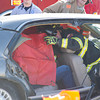 Ben Weaver of the Goose Valley Volunteer Fire Department shields the occupants in the back seat with a tarp as rescue crews cut away glass and metal to free them.