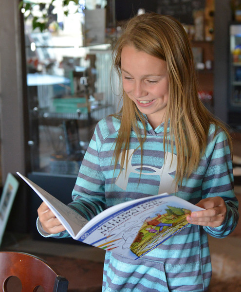 "Justin Sheely | The Sheridan Press<br /> Twelve-year-old Chloe Wilson flips through a coloring book by local artist Andy Robbins ""Yellowstone National Park: A Cautionary Coloring Book"" during a book signing Thursday at Gina's Gallery in Dayton. The coloring book, which is recommended for mature readers, depicts careless tourists being killed or endangering themselves at Yellowstone National Park."