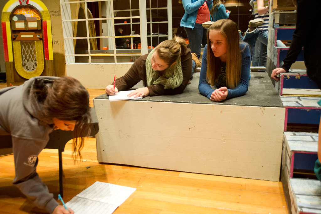 Students Becky Bridger, left, Morgan Parker and Madison Bland review a scene during a rehearsal of 'Grease' Wednesday, Jan. 22, 2014 in the Sue Henry auditorium at Sheridan High School.