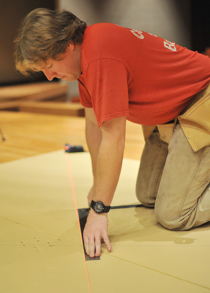 Grease Set Designer Philip Garber uses a laser to draw a line while working on a stage piece Saturday, Jan. 25, 2014 at Sheridan High School.